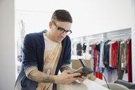 Man using credit card reader in shop - HEROF02711