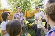 Multi-generation family enjoying lemonade in backyard - HEROF02726