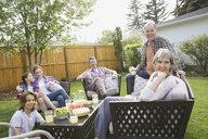 Multi-generation family relaxing in backyard - HEROF02732
