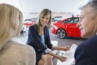 Saleswoman and couple finalizing paperwork in car dealership - HEROF02771