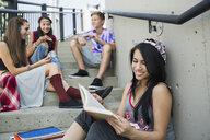 Teenage girl reading book on stairs - HEROF02969
