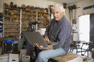 Senior man using laptop in workshop - HEROF03035