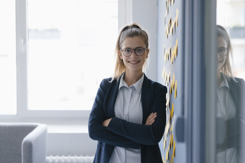 Portrait of a confident young businesswoman, standing in office - GUSF01676