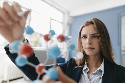Female scientist studying molecule model - GUSF01679