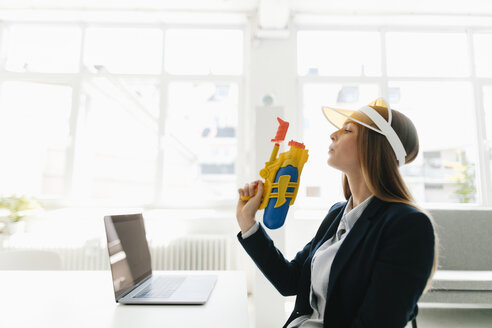 Young businesswoman, holding water gun - GUSF01685
