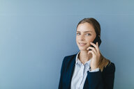 Portrait of a young businesswoman against blue background, talking on her smartphone - GUSF01688