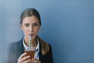 Portrait of a young businesswoman against blue background, drinking iced tea with a straw - GUSF01691