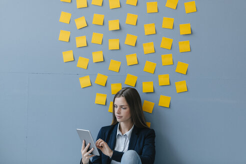 Young businesswoman usig digital tabet, sitting under data cloud - GUSF01712