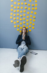 Young businesswoman sitting under data cloud, meditating - GUSF01718