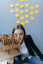 Young businesswoman holding architectural model with yellow sticky notes on the wall behind ger - GUSF01721