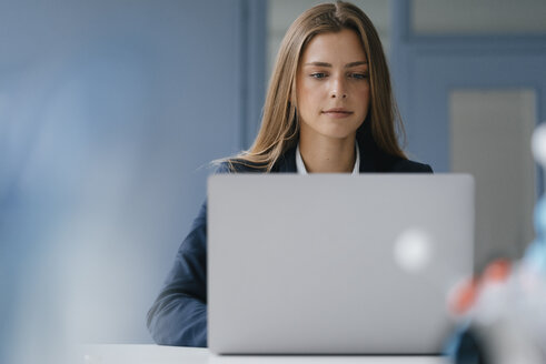 Portrait of a young businesswoman, working in office, using laptop - GUSF01733