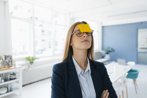 Young businesswman with yellow sticky note on her forehead - GUSF01745