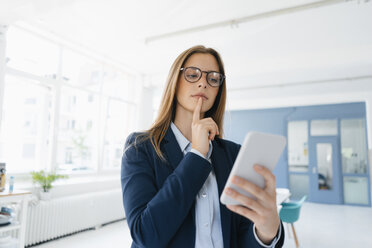 Young businesswoman using smartphone in office - GUSF01748