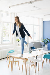 Young businesswoman balancing on one leg on desk in the board room - GUSF01760