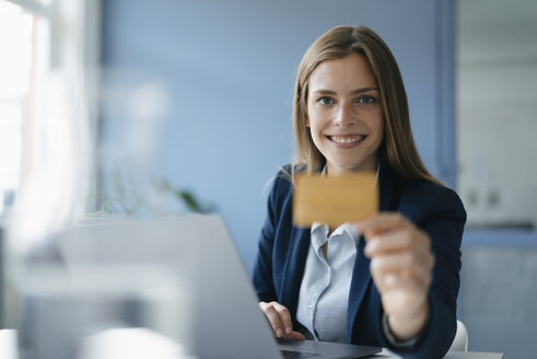 Young businesswoman doing online payment, showing her credit card - GUSF01772