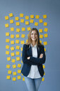 Yong businesswoman standing in front of wall, full of yellow sticky notes, with arms crossed - GUSF01778