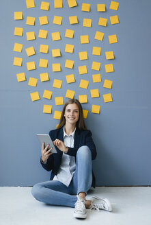 Young businesswoman usig digital tabet, sitting under data cloud - GUSF01781