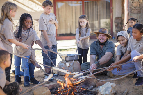 Children and guide roasting twist bread at camp fire - ZEF16087