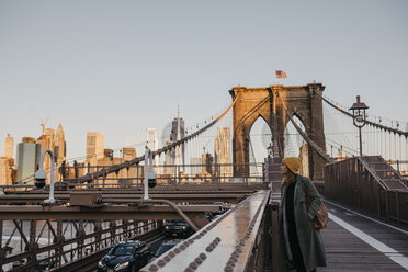 USA, New York, New York City, female tourist on Brooklyn Bridge in the morning light - LHPF00316