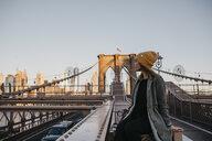 USA, New York, New York City, female tourist sitting on Brooklyn Bridge in the morning light - LHPF00319