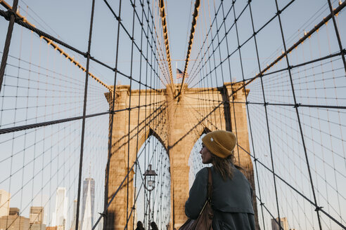 USA, New York, New York City, female tourist on Brooklyn Bridge in the morning light - LHPF00322