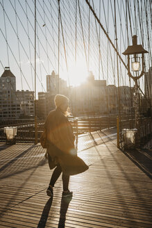 USA, New York, New York City, female tourist on Brooklyn Bridge at sunrise - LHPF00325