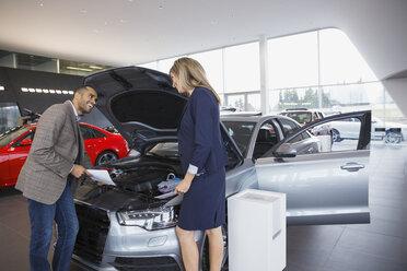 Saleswoman and man looking at engine in showroom - HEROF03116