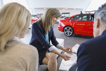 Saleswoman and couple finalizing paperwork in car dealership - HEROF03179