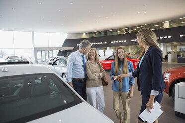 Saleswoman handing family key in car dealership showroom - HEROF03200