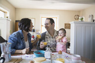 Young family enjoying breakfast at dining table - HEROF03257