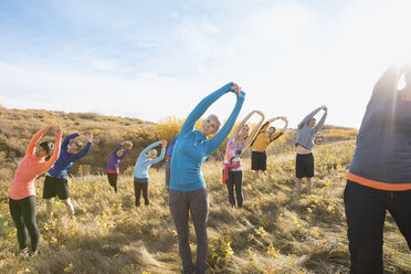 Group fitness stretching in sunny rural field - HEROF03353