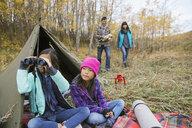 Sisters with binoculars outside tent - HEROF03356