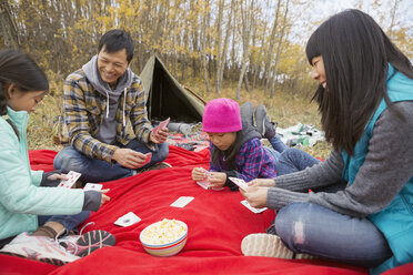 Family playing cards at campsite - HEROF03359