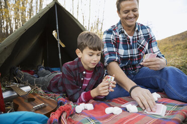 Father and son playing cards outside tent - HEROF03368