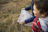 Father and son with treasure map in field - HEROF03371