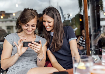 Two women having fun with their smartphone on a terrace - MGOF03882