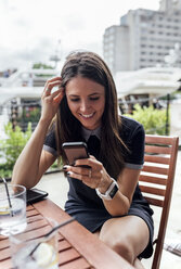 Young beautiful woman using her smartphone on a terrace - MGOF03888