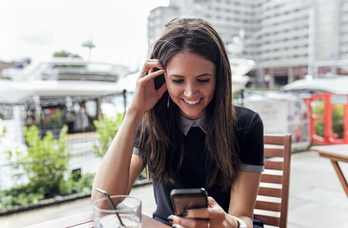 Young beautiful woman using her smartphone on a terrace - MGOF03891