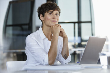 Smiling businesswoman sitting at desk in office with laptop - RBF06853