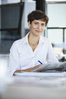 Portrait of confident businesswoman sitting at desk in office with laptop and document - RBF06856