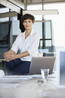 Portrait of confident businesswoman sitting on desk in office with laptop - RBF06859