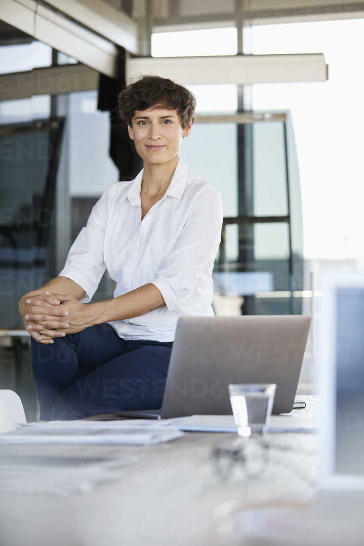 Portrait of confident businesswoman sitting on desk in office with laptop - RBF06859 - Rainer Berg/Westend61