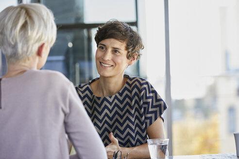 Two businesswomen talking at desk in office - RBF06880