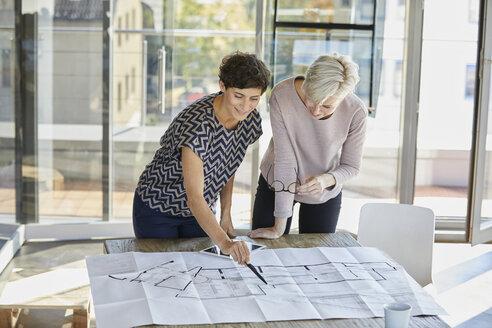 Two smiling businesswomen discussing floor plan on desk in office - RBF06883