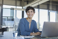 Smiling businesswoman sitting at desk in office with laptop - RBF06886