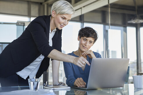 Two smiling businesswomen sharing laptop at desk in office - RBF06889