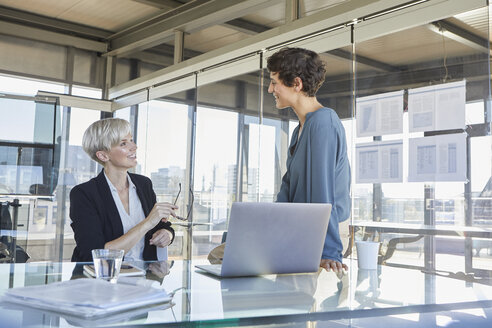 Two smiling businesswomen discussing at desk in office - RBF06895