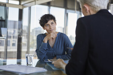 Two businesswomen talking at desk in office - RBF06901