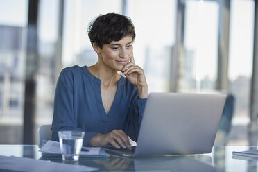 Businesswoman sitting at desk in office using laptop - RBF06904