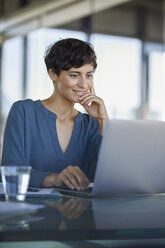 Businesswoman sitting at desk in office using laptop - RBF06907